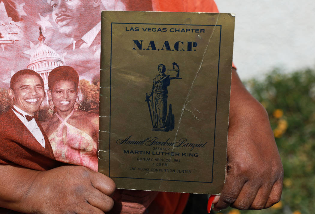 Gwen Walker, owner of the Walker African-American Museum & Research Center, poses for a photograph with a program from the Las Vegas chapter's NAACP Freedom Banquet in 1964, which featured Dr. ...