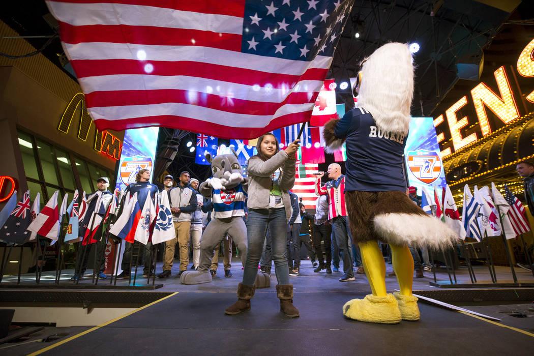 La abanderada Aaliyah Sanchez, de cuarto grado en la Escuela Primaria Vegas Verde, ondea la bandera estadounidense cuando se presenta el equipo USA Rugby Sevens durante el Desfile de las Naciones ...