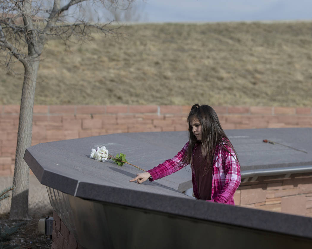 Ava Gallegos reads inscriptions honoring victims of the Columbine school shooting on Wednesday, March 14, 2018, at the Columbine Memorial, in Littleton, CO. Eric Harris and Dylan Klebold, seniors  ...
