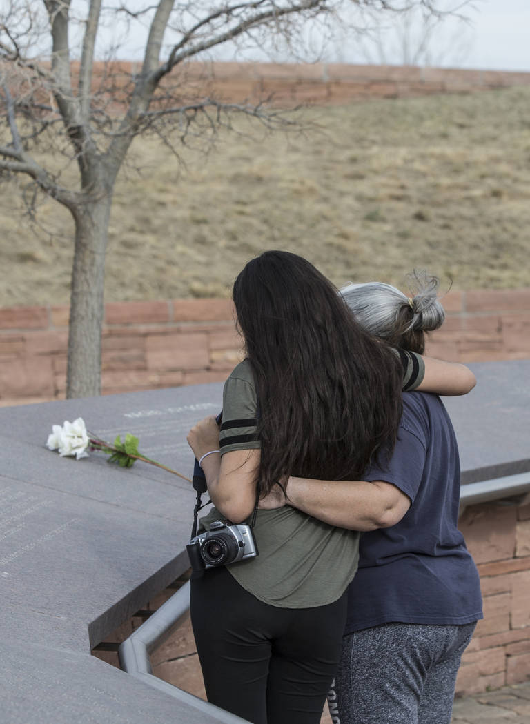 Alexia Narro, left, and Sharon Gallegos read inscriptions honoring victims of the Columbine school shooting on Wednesday, March 14, 2018, at the Columbine Memorial, in Littleton, CO. Eric Harris a ...