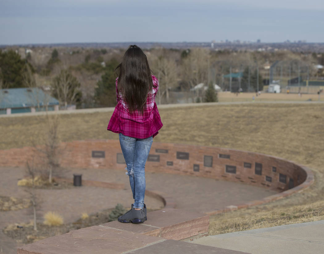 Ava Gallegos looks down upon the Columbine Memorial on Wednesday, March 14, 2018, in Littleton, CO. Eric Harris and Dylan Klebold, seniors at Columbine High School, shot and killed 13 people and i ...