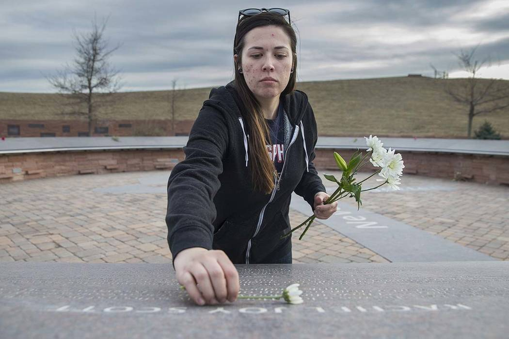 """Sierra Evans places flowers on stones honoring victims of the Columbine school shooting on Wednesday, March 14, 2018, at the Columbine Memorial, in Littleton, CO. """"We have a beautiful memoria ..."""