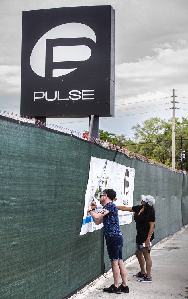 Jose Nieves, left, and Odette Morillo write messages on a banner outside Pulse nightclub on Monday, March 19, 2018, in Orlando, FL. Omar Mateen killed 49 people and wounded 58 inside the club on J ...