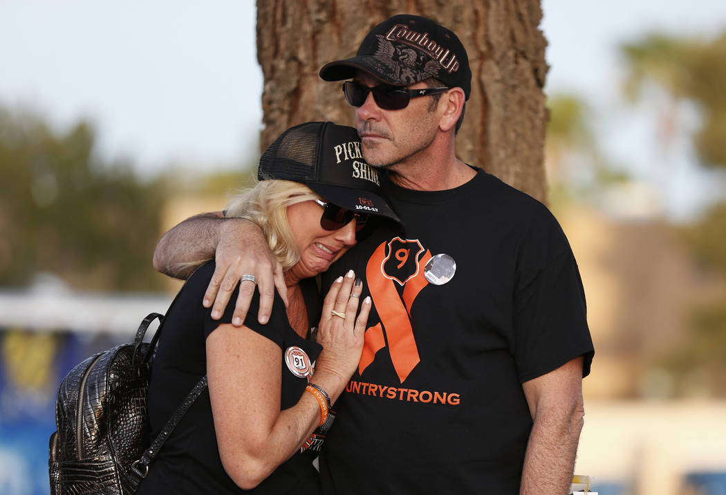 Tracey Duden is embraced by her husband John while a song that he wrote with his band, Pickleback Shine, plays during the Route 91 Candlelight Vigil near Mandalay Bay in Las Vegas on Sunday, April ...