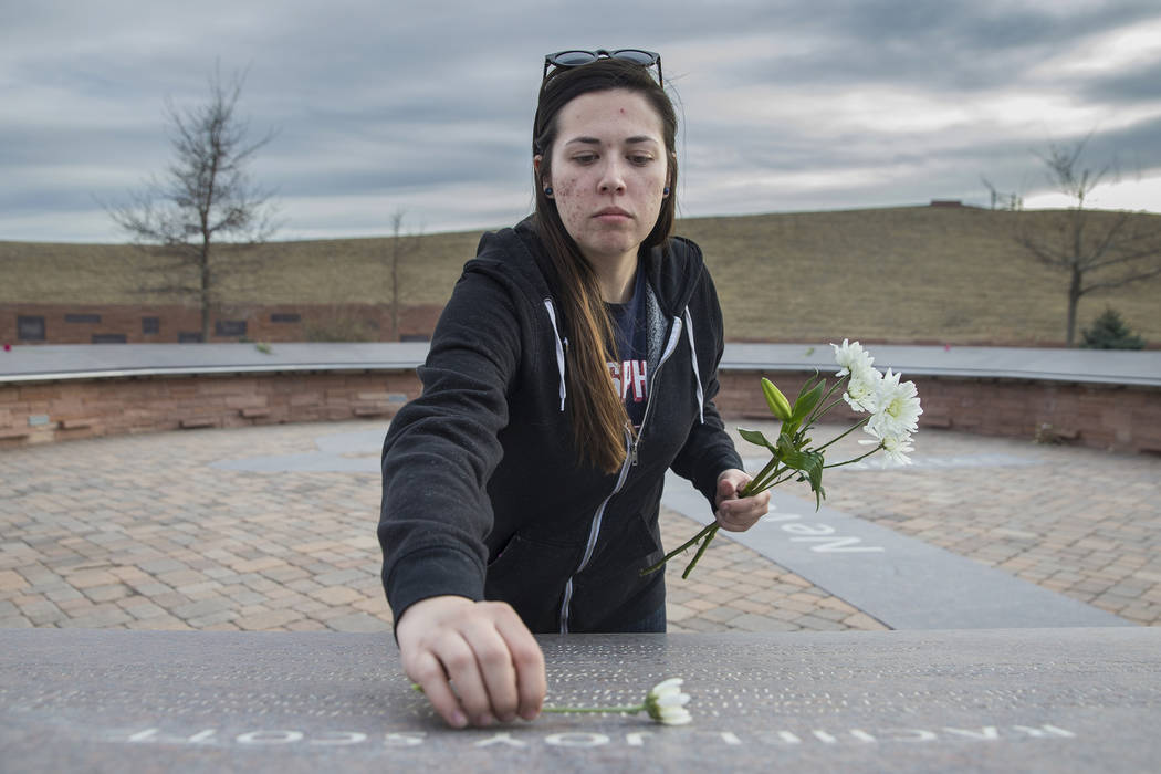 "Sierra Evans places flowers on stones honoring victims of the Columbine school shooting on Wednesday, March 14, 2018, at the Columbine Memorial, in Littleton, CO. ""We have a beautiful memoria ..."