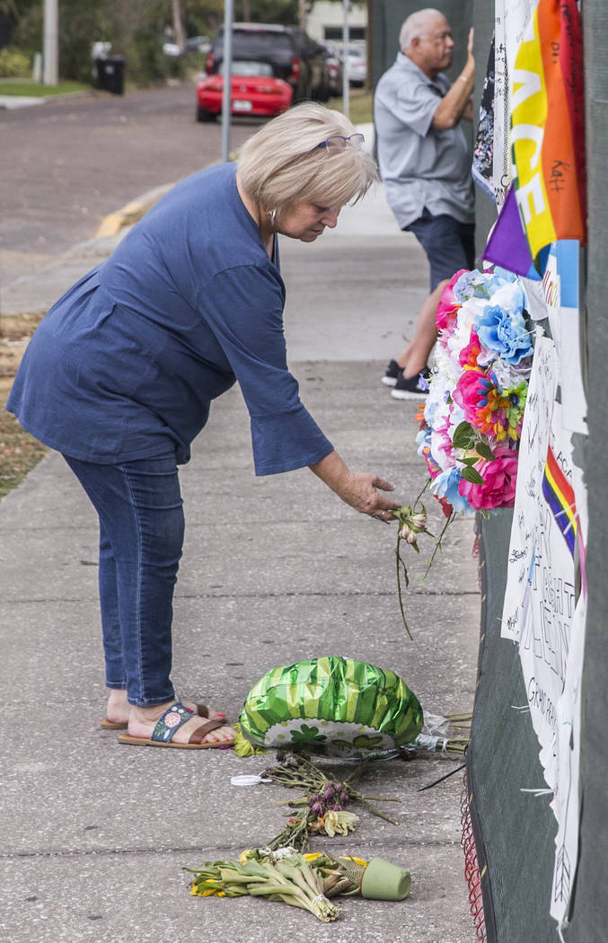 Michele Petno, left, straightens a floral wreath on the fence outside Pulse nightclub on Monday, March 19, 2018, in Orlando, FL. Omar Mateen killed 49 people and wounded 58 inside the club on June ...