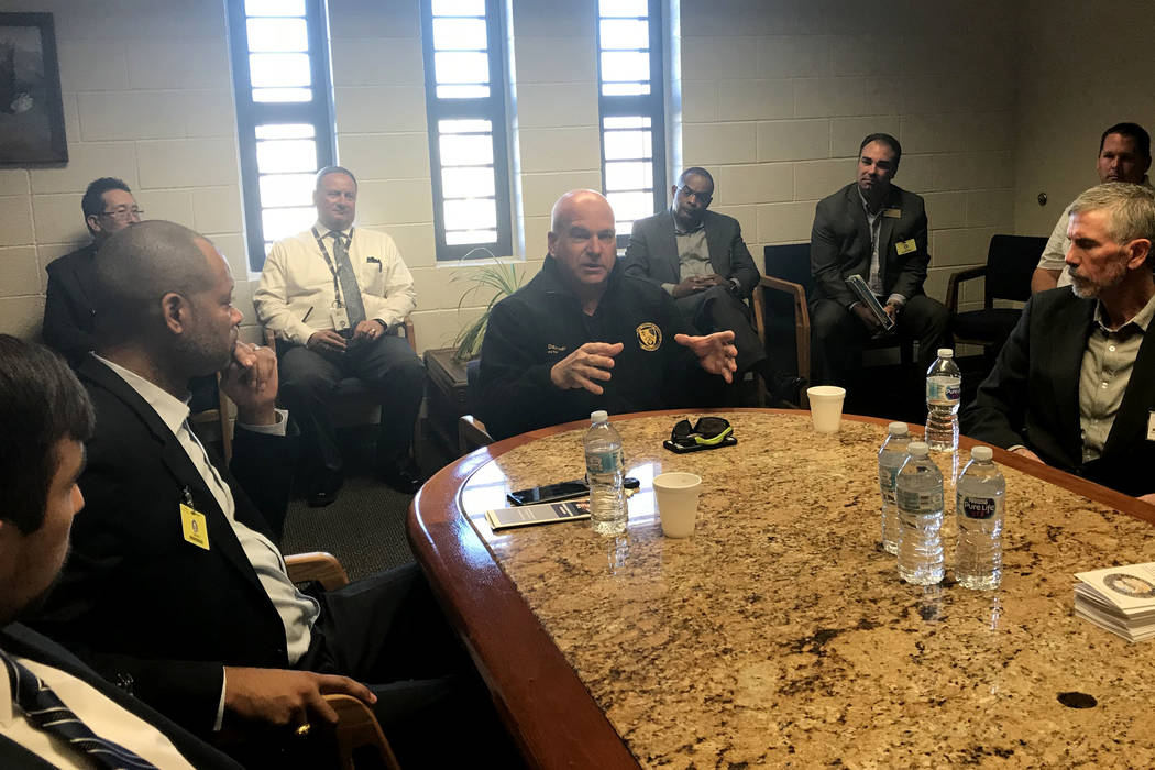 James Dzurenda, director of the Nevada Department of Corrections, center, talks to higher education officials and Senate Majority Leader Aaron Ford, second from left, on Friday, March 30, 2018, at ...