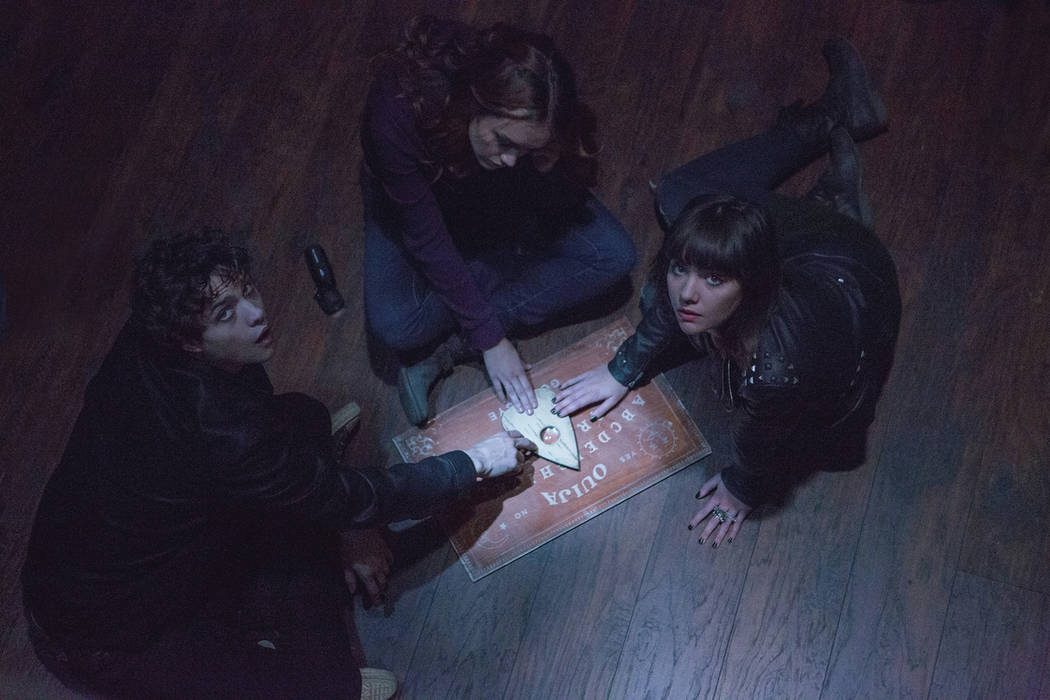 "(L to R) Pete (DOUGLAS SMITH), Laine (OLIVIA COOKE) and Sarah (ANA COTO) play the game in ""Ouija"", a supernatural thriller about a group of friends who must confront their most terrifyin ..."