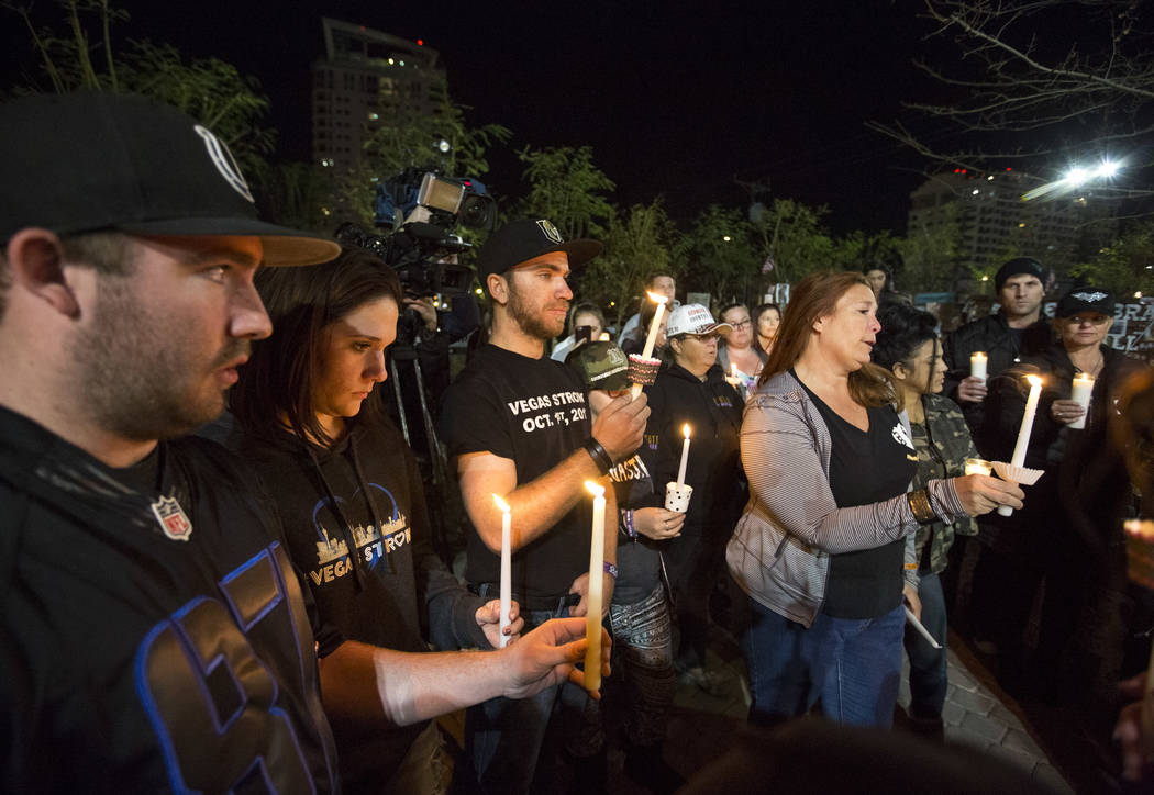 Cody Dion, from left, his girlfriend Rylie Golgart, Zach Laswell and Heather Gooze attend a candlelight vigil at the Las Vegas Community Healing Garden on Friday, Feb. 16, 2018, to honor victims o ...