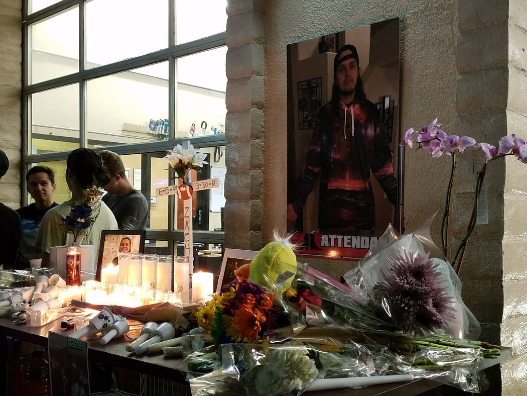 Candles, flowers and photos adorn a memorial to Zach Ragusa, who was killed in a shooting Friday morning at Terrible's Car Wash & Lube in Henderson. The memorial was seen at a vigil held Saturda ...