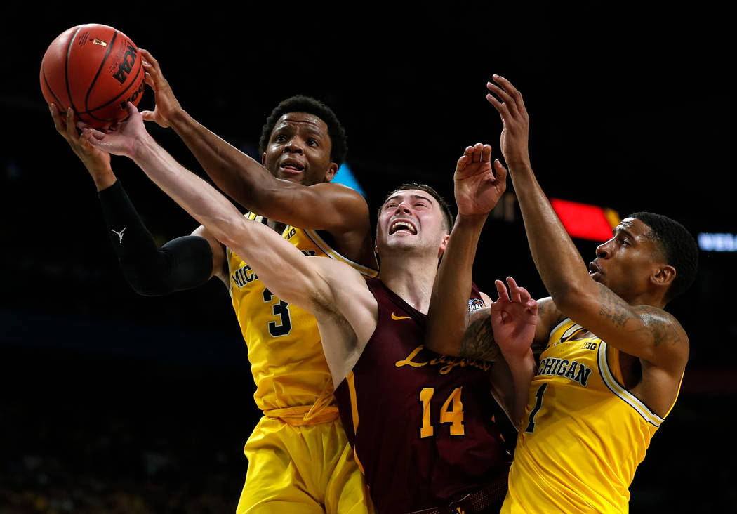 Loyola-Chicago guard Ben Richardson (14) fights for a rebound with Michigan guard Zavier Simpson, left, and Charles Matthews, right, during the second half in the semifinals of the Final Four NCAA ...