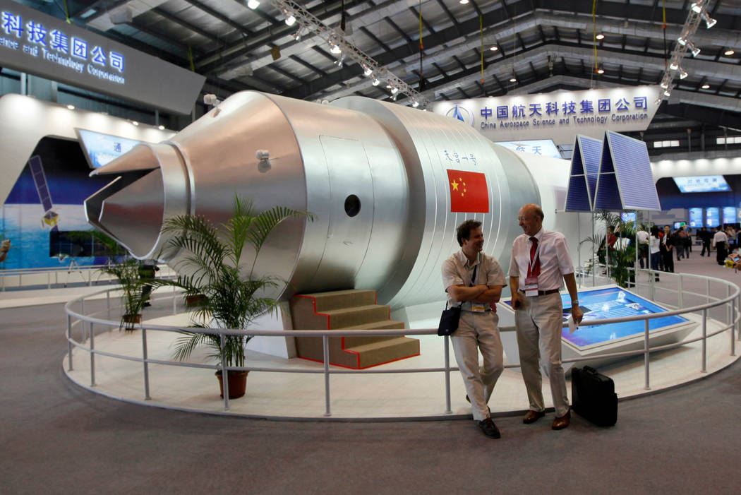 Visitors sit beside a model of China's Tiangong-1 space station at the 8th China International Aviation and Aerospace Exhibition in Zhuhai in southern China's Guangdong Province, Nov. 16, 2010. Ch ...