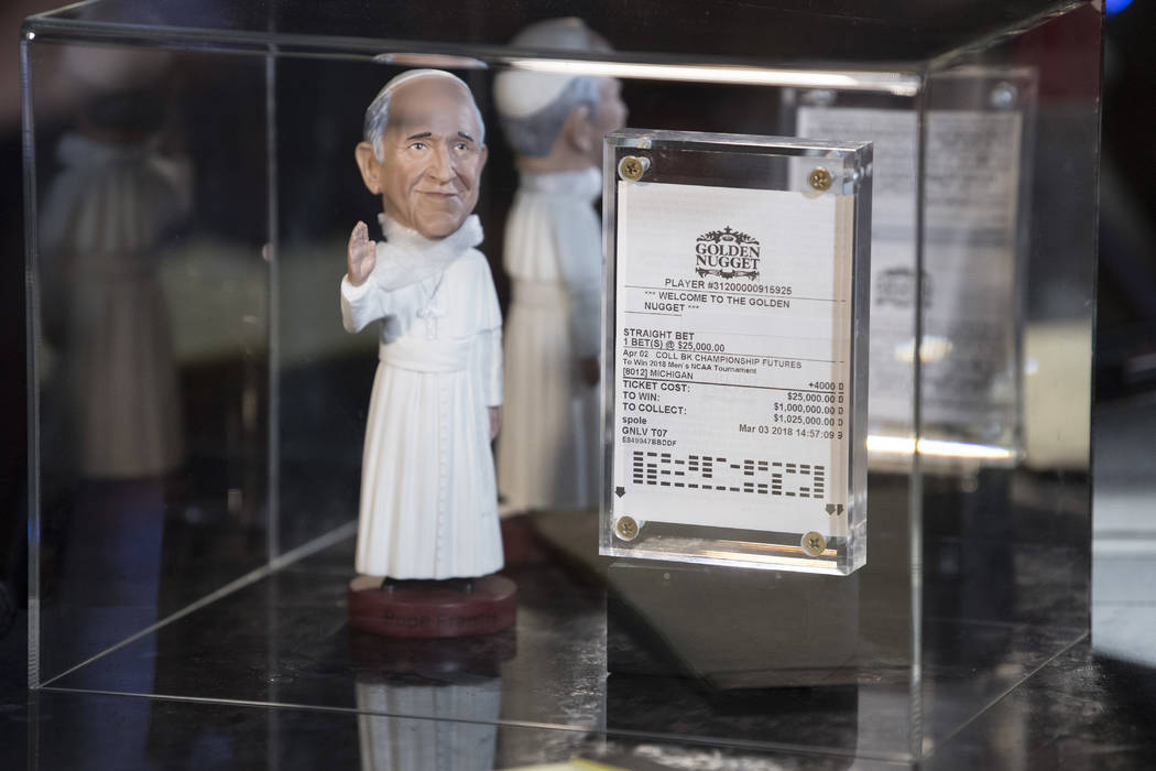 His betting slip and a figure of Pope Francis sits under a box as Derek Stevens, CEO and co-owner of The D Las Vegas, watches his alma mater Michigan take on Loyola in the Final Four Saturday, Mar ...