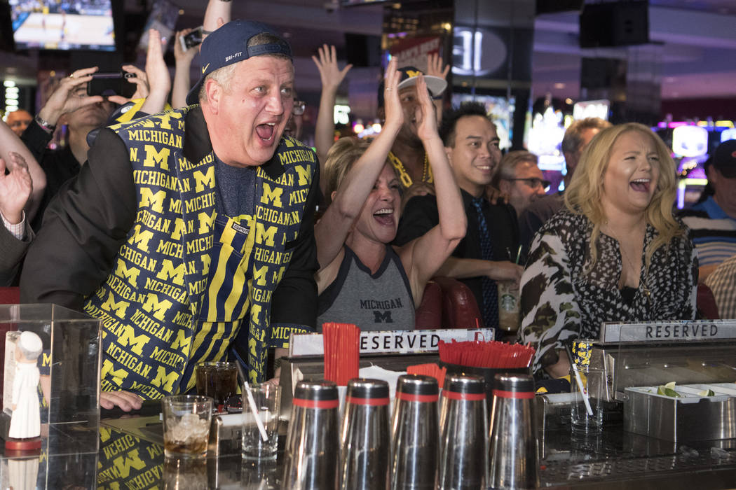 Derek Stevens, CEO and co-owner of The D Las Vegas, reacts along with his wife Nicole, center, and daughter Whitney while watching his alma mater Michigan take on Loyola in the Final Four Saturday ...