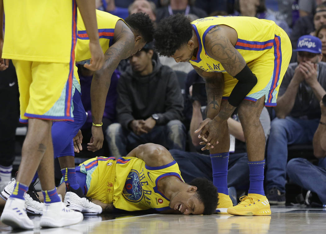 Golden State Warriors guard Patrick McCaw lays on the court in pain as teammates Jordan Bell, left and Nick Young check on his condition after falling hard to the floor late in the third quarter f ...