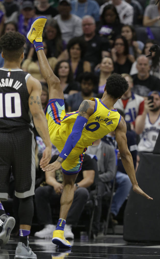 Golden State Warriors guard Patrick McCaw, right, falls to the court following a Flagrant 1 foul by Sacramento Kings's Vince Carter in an NBA basketball game Saturday, March 31, 2018, in Sacrament ...