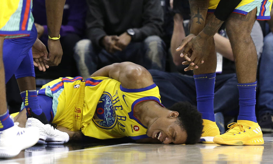 Golden State Warriors guard Patrick McCaw lays on the court in pain after falling hard to the floor late in the third quarter following a Flagrant 1 foul by Sacramento Kings's Vince Carter in an N ...