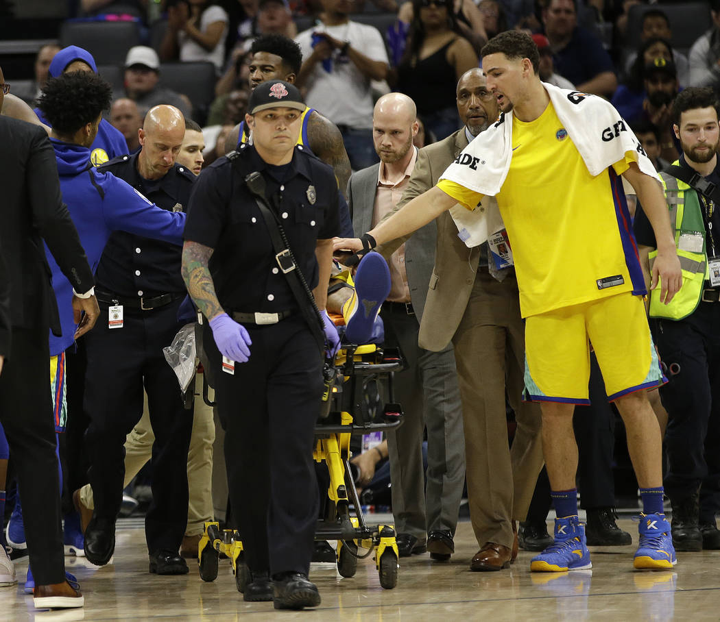 Golden State Warriors guard Klay Thompson, right, reaches out to teammate Patrick McCaw as he is taken off the court on a stretcher after falling hard to the floor late in the third quarter follow ...