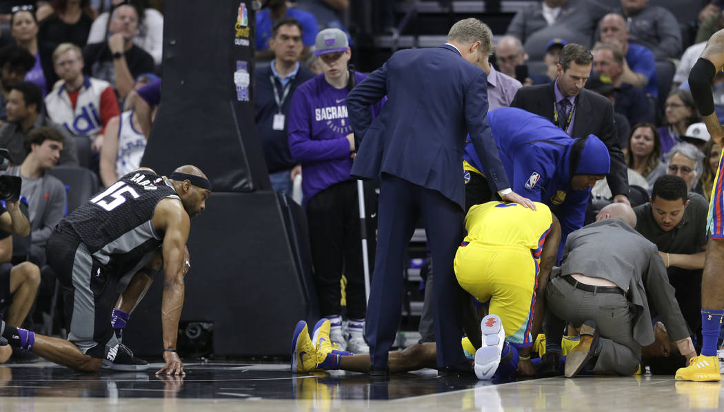 Sacramento Kings forward Vince Carter, left, watches as Golden State Warriors' Patrick McCaw is tended to after Carter's Flagrant-1 foul caused him to land hard on the court during the third quart ...