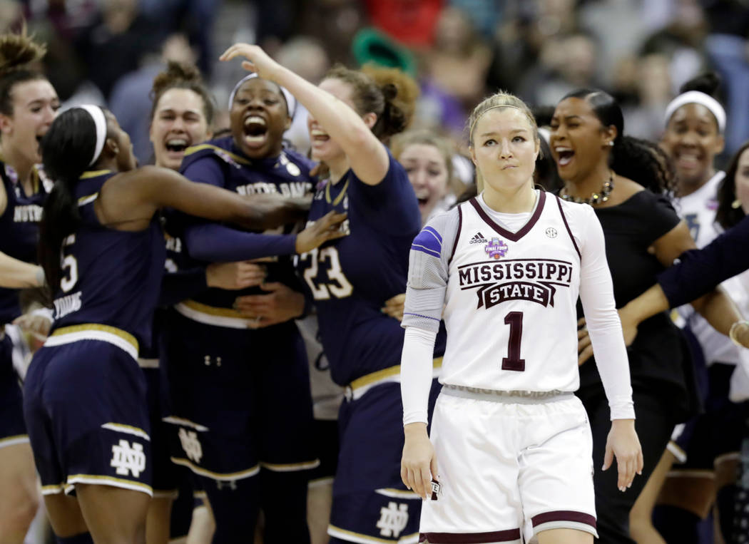 Notre Dame's Arike Ogunbowale is congratulated by teammates as Mississippi State's Blair Schaefer (1) walks away after Ogunbowale made a 3-point basket to defeat Mississippi State 61-58 in the fin ...
