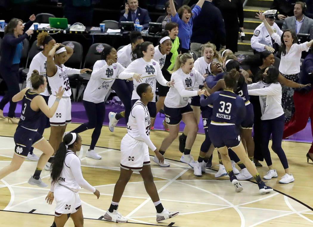 Notre Dame's Arike Ogunbowale is mobbed by teammates after sinking a 3-point basket to defeat Mississippi State 61-58 in the final of the women's NCAA Final Four college basketball tournament, Sun ...