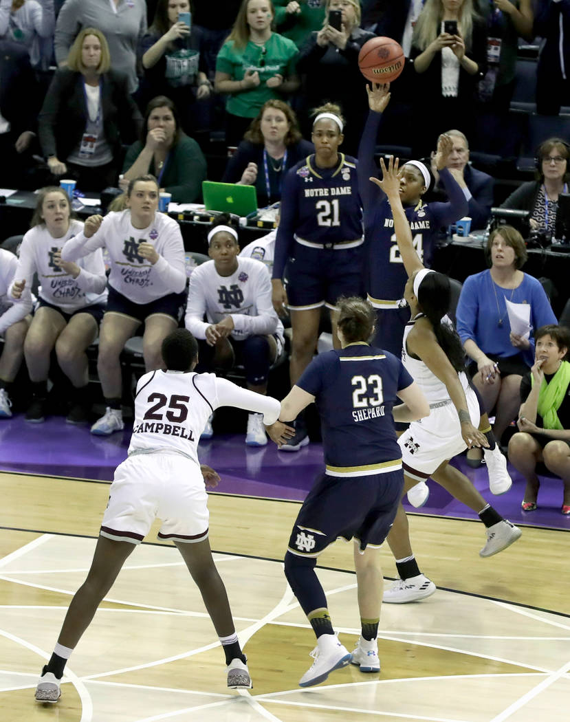 Notre Dame's Arike Ogunbowale, top, sinks a 3-point basket to defeat Mississippi State 61-58 during the second half in the final of the women's NCAA Final Four college basketball tournament, Sunda ...