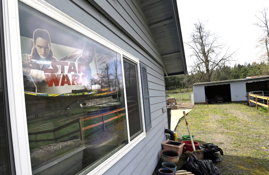 This photo taken Wednesday, March 28, 2018, shows a Stars Wars poster in the garage window with a small horse stable at right at the house in Woodland, Wash., where the Hart Family lived. (AP Phot ...