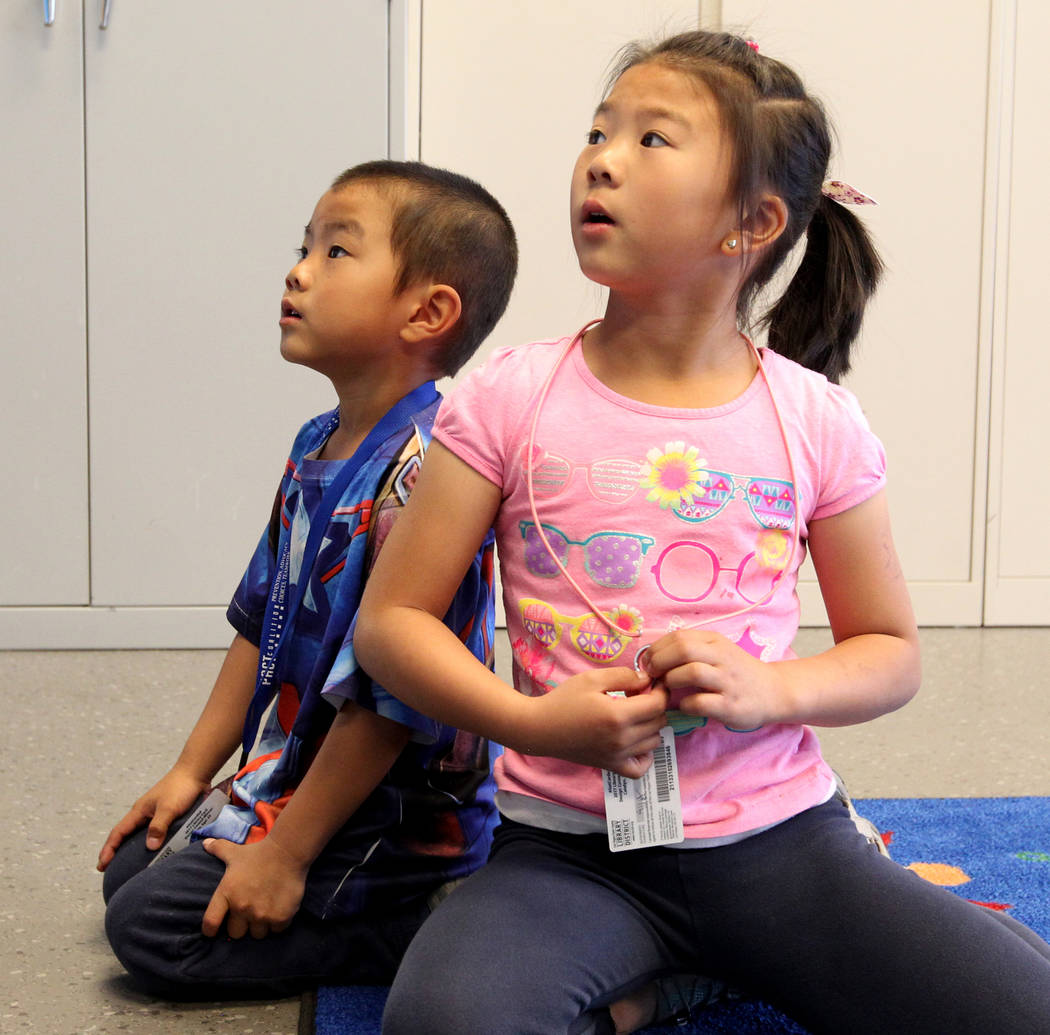 Ethan Chen, 5, and his sister Ally Chen, 7, listen to Mallory Snow, Young People's Library assistant at Clark County Library on Flamingo Road near Maryland Parkway reads to, during Storytime Monda ...