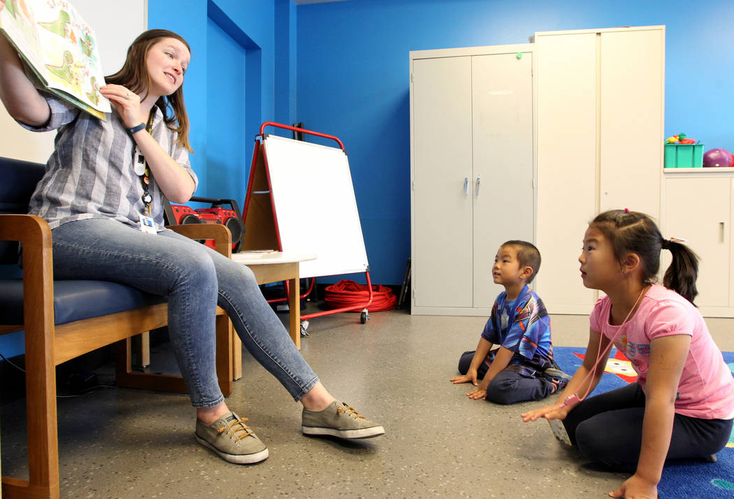 Mallory Snow, Young People's Library assistant at Clark County Library on Flamingo Road near Maryland Parkway reads to Ethan Chen, 5, and his sister Ally Chen, 7, during Storytime Monday, April 2, ...