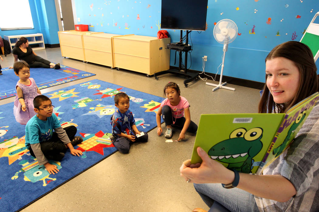 Mallory Snow, Young People's Library assistant at Clark County Library on Flamingo Road near Maryland Parkway, reads to, from left, Emy Ma, 2, Edison Zhang, 10, Ethan Chen, 5, and Ally Chen, 7, du ...