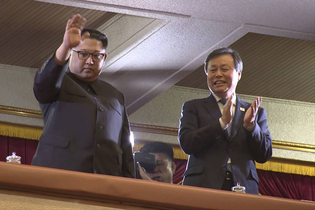 In this Sunday, April 1, 2018, image from video, North Korean leader Kim Jong Un, left, waves as South Korean Culture, Sports and Tourism Minister Do Jong-whan claps during a performance by a Sout ...