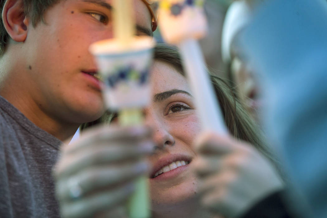 """Allie Rossi, center, is comforted by Brennan Mecke while mourning the loss of her brother, Albert """"A.J."""" Rossi, during a candlelight vigil at Knickerbocker Park in Las Vegas Friday, Marc ..."""