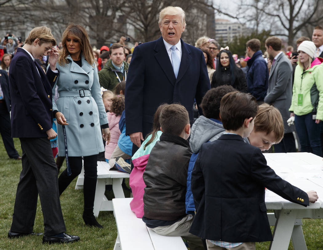 President Donald Trump, with first lady Melania Trump and their son Barron Trump move to sit with children writing cards for troops at the White House in Washington, Monday, April 2, 2018, during  ...
