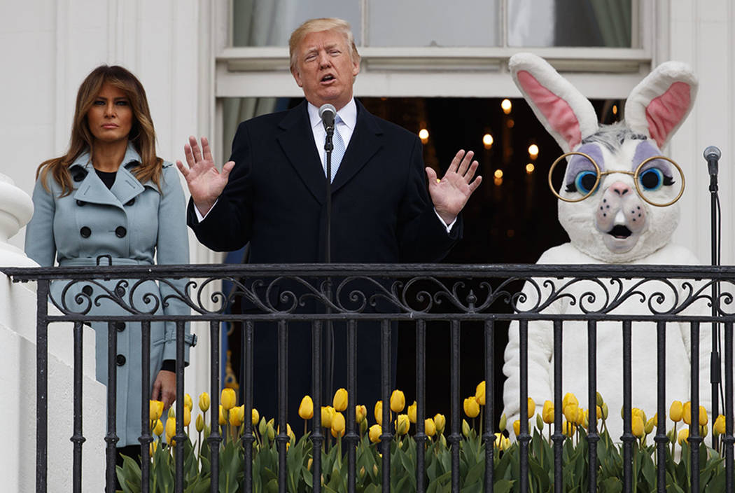 President Donald Trump, joined by the Easter Bunny and first lady Melania Trump speaks from the Truman Balcony of he White House in Washington, Monday, April 2, 2018, during the annual White House ...