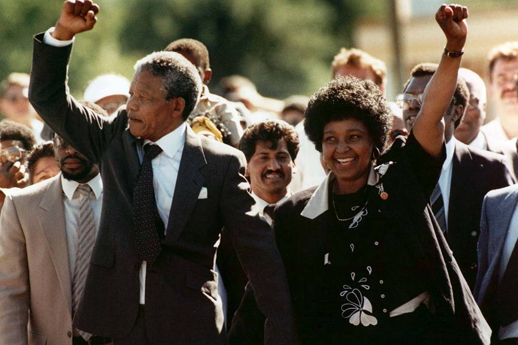 In this file photo dated Sunday, Feb. 11, 1990, Nelson Mandela and wife Winnie, walk hand-in-hand, raising their clenched fists upon his release from Victor prison, Cape Town, 27 years in detentio ...