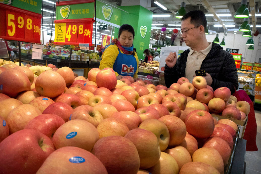 A woman wearing a uniform with the logo of an American produce company helps a customer shop for apples a supermarket in Beijing, March 23, 2018. China raised import duties on a $3 billion list of ...