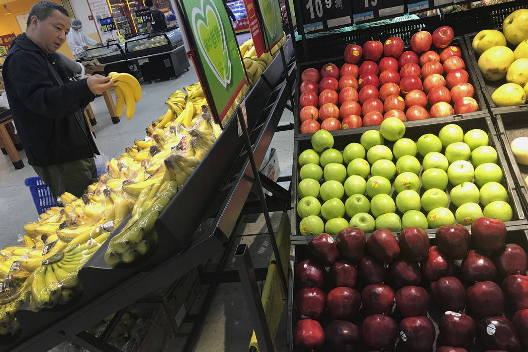 A man chooses bananas near imported apples from the United States at a supermarket in Beijing, Monday, April 2, 2018.  China raised import duties on a $3 billion list of U.S. pork, fruit and other ...
