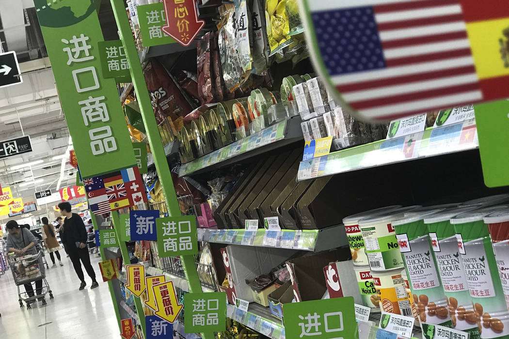 Women push a shopping cart near nuts and sweets imported from the United States and other countries displayed on a section selling imported foods at a supermarket in Beijing, Monday, April 2, 2018 ...