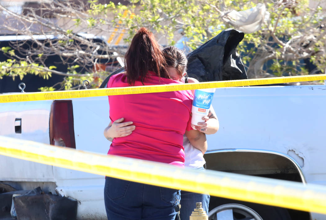 Two women comfort each other outside a home at 2510 Daley St., near Las Vegas Boulevard North and Carey Avenue, as North Las Vegas police investigate a homicide on Thursday, March 29, 2018. (Bizua ...