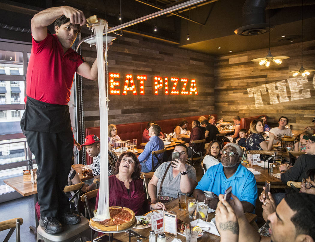 Server Gonzalo Acera, left, stretches mozzarella cheese nearly 10 feet high while serving an extra cheese deep dish pizza at Giordano's on Sunday, March 26, 2017, in Las Vegas. (Benjamin Hager/Las ...