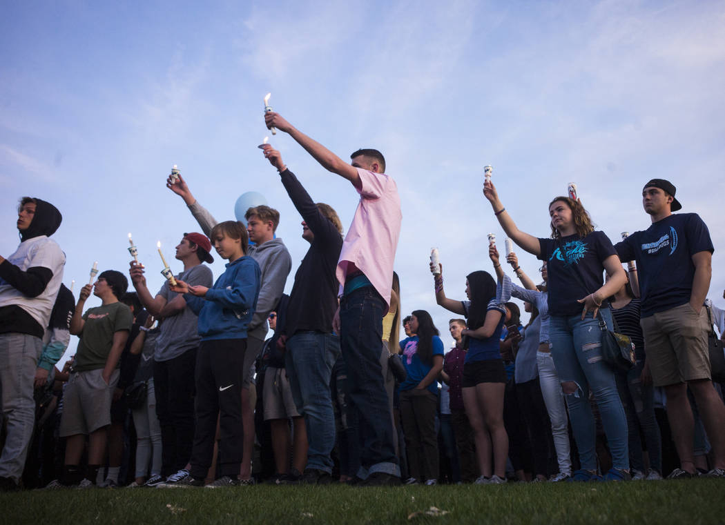 "Attendees during a candlelight vigil at Knickerbocker Park in Las Vegas Friday, March 30, 2018 for Centennial High School students Albert ""A.J."" Rossi, Dylan Mack and Brooke Hawley, who  ..."