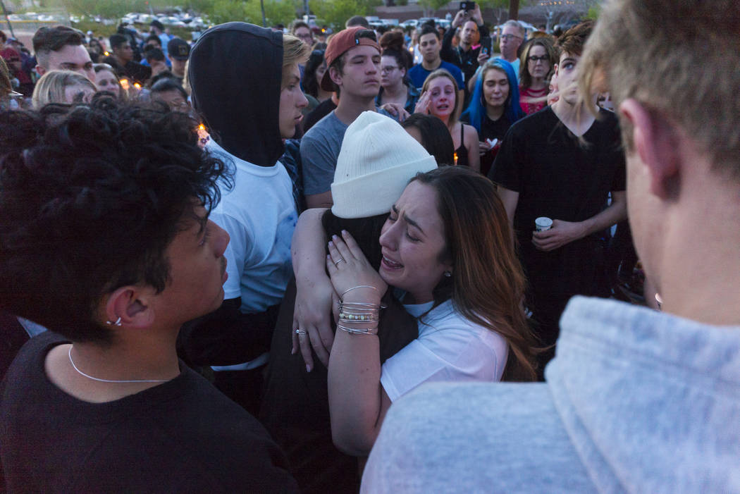"Allie Rossi, right, mourns the loss of her brother, Albert ""A.J."" Rossi, while hugging Alexis Vargas during a candlelight vigil at Knickerbocker Park in Las Vegas Friday, March 30, 2018. ..."