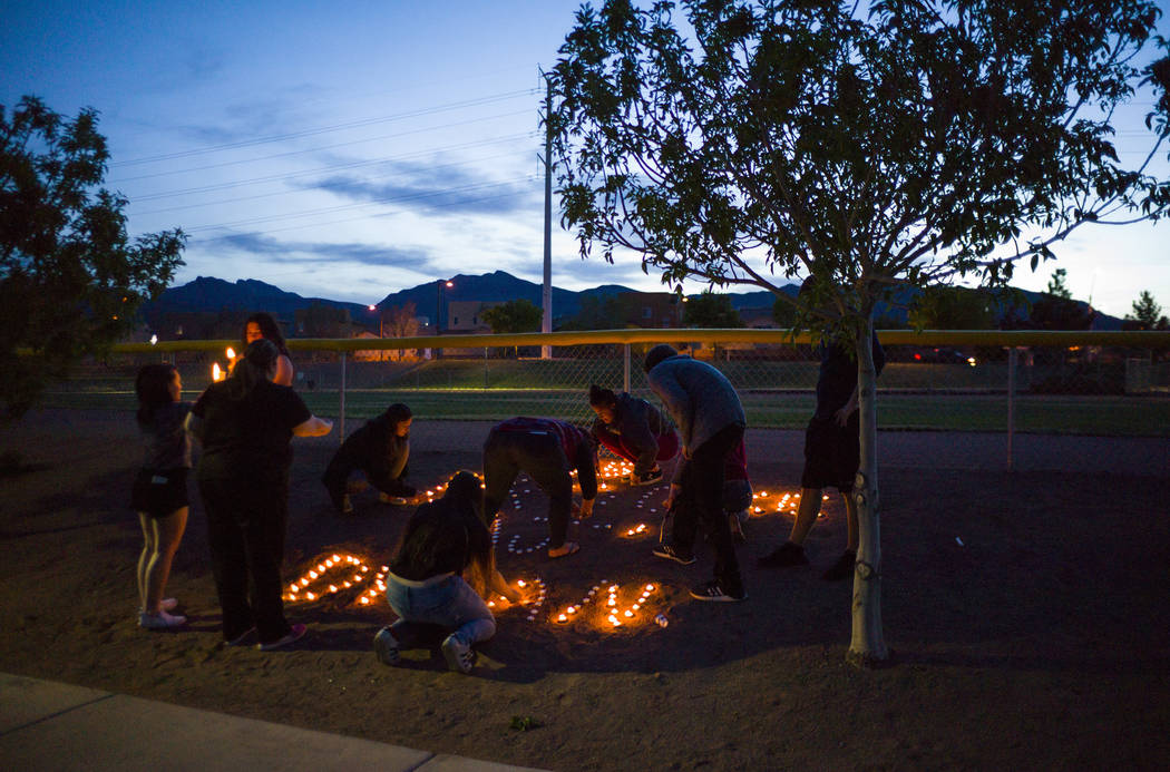 "Attendees lay out candles following a vigil at Knickerbocker Park in Las Vegas Friday, March 30, 2018 for Centennial High School students Albert "" A.J."" Rossi, Dylan Mack and Brooke Hawl ..."