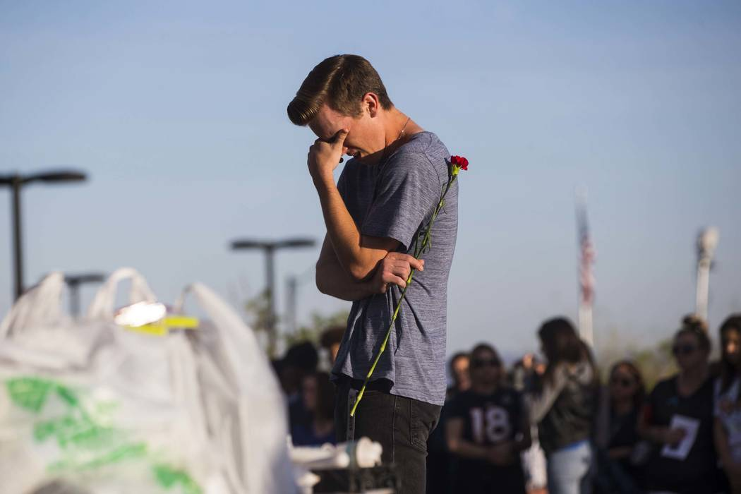 An attendee reacts during a candlelight vigil at Knickerbocker Park in Las Vegas Friday, March 30, 2018 for Centennial High School students Albert ÒA.J.Ó Rossi, Dylan Mack and Brooke Haw ...