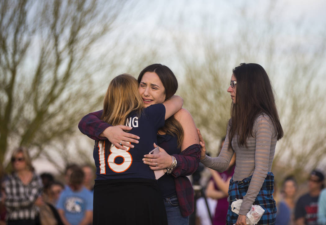 "Allie Rossi, center, is comforted while mourning the loss of her brother, Albert ""A.J."" Rossi, during a candlelight vigil at Knickerbocker Park in Las Vegas Friday, March 30, 2018. Alber ..."