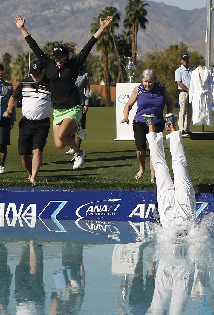 Pernilla Lindberg, second from left, jumps into the pond with her parents and caddie/fiancee Daniel Taylor, right, after winning the LPGA Tour ANA Inspiration golf tournament on the eighth playoff ...