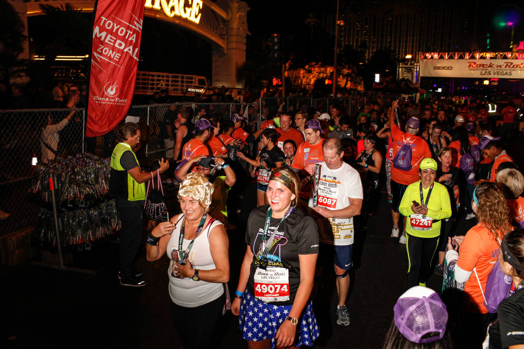 Angela Newman, left, and her daughter Siona Neumann, right, both of Germany, cross the finish line at the 10K run of the Rock 'n' Roll Las Vegas Marathon along the Strip near The Mirage in Las Veg ...