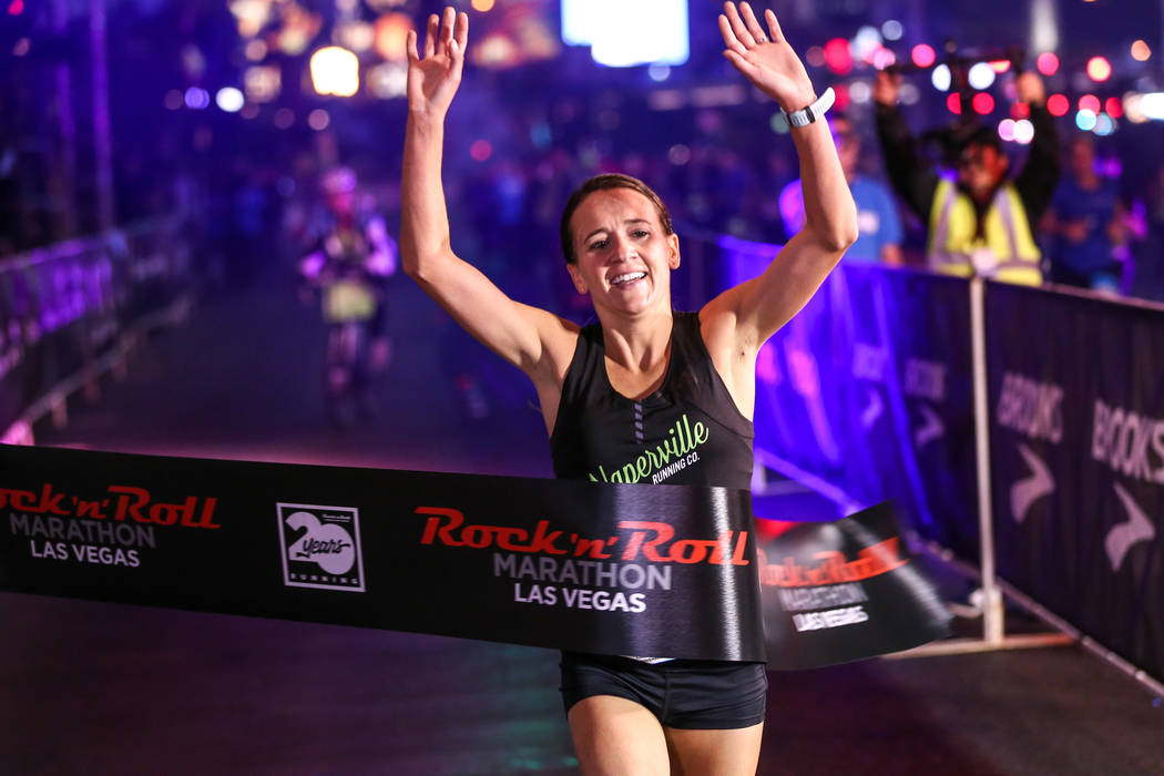 Marisa Hird of Naperville, Illinois crosses the finish line winning first place at the women's marathon run of the Rock 'n' Roll Las Vegas Marathon along the Strip near The Mirage in Las Vegas, Su ...