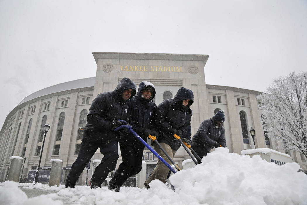Men shovel snow from the sidewalks in front of Yankee Stadium before the New York Yankees home opener against the Tampa Bay Rays, Monday, April 2, 2018, in New York. (AP Photo/Seth Wenig)
