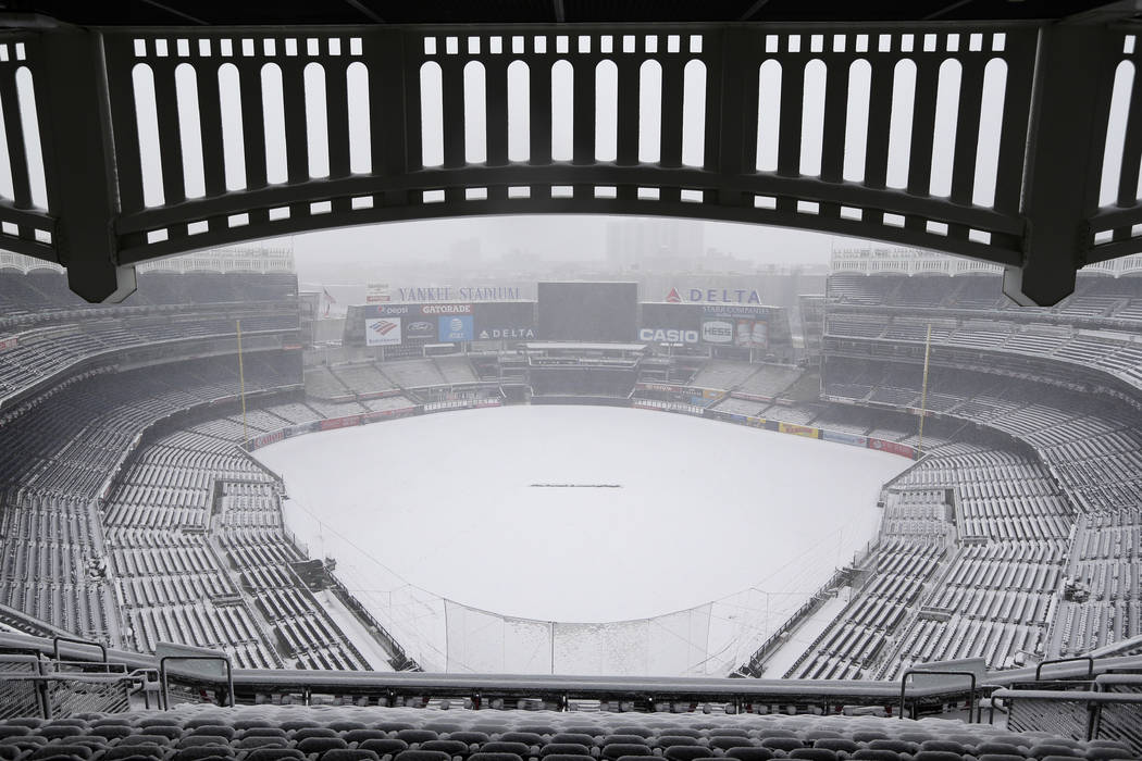 Snow covers the field before a scheduled New York Yankees' home opener game against the Tampa Bay Rays at Yankee Stadium Monday, April 2, 2018 in New York. The game was postponed due to weather an ...